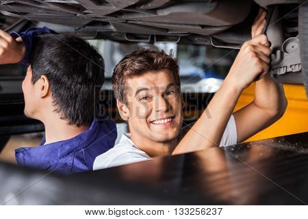 Happy Mechanic Working Under Lifted Car With Colleague