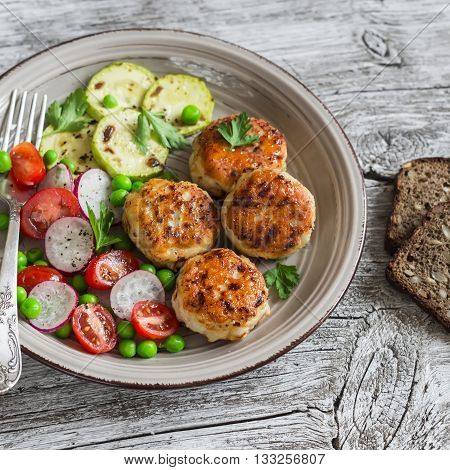 Chicken cutlets grilled zucchini and fresh vegetable salad on rustic light wood background