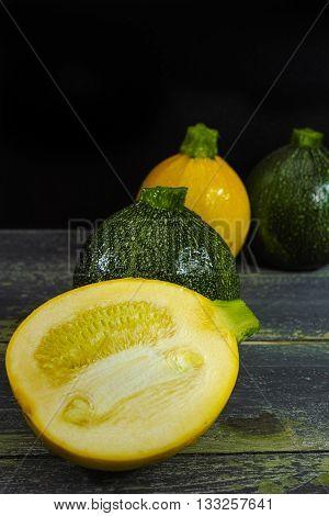 Yellow and green fresh zucchini (Cucurbita pepo) on a dark background