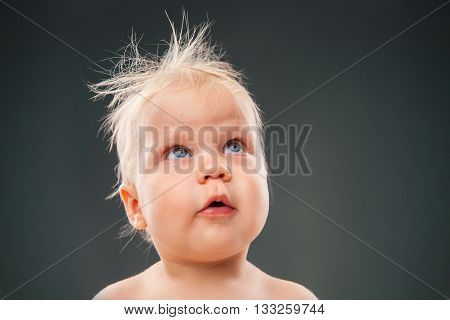 Portrait of blonde baby with messy hair looking up.Studio shot