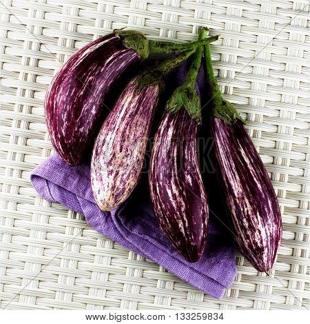 Arrangement of Fresh Raw Striped Eggplants on Purple Napkin closeup on Wicker background