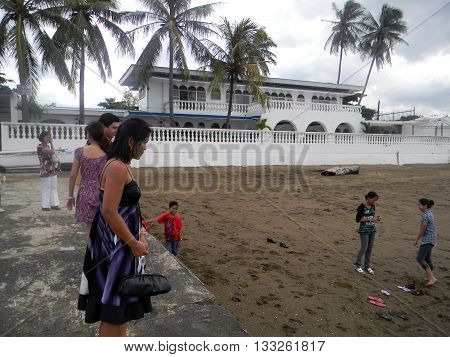 CEBU CITY, CEBU / PHILIPPINES - JULY 30, 2011: People enjoy the beach in front of a large beachfront mansion in Cebu.