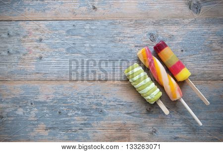 Three frozen ice lollies on a wooden background