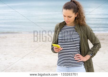 Young girl in a green jacket uses yellow mobile phone on the beach