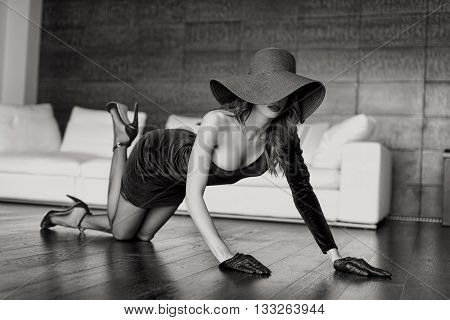 Sexy rich woman in hat kneeling on the floor black and white
