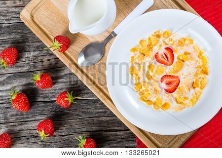 healthy corn flakes with milk and strawberries in a white dish with jug of milk on a cutting board on an old rustic table studio lights close-up view from above