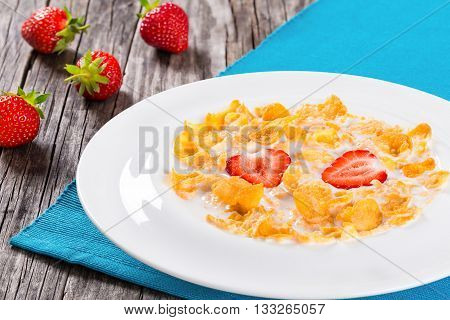 healthy corn flakes with milk and strawberries in a white dish on an old rustic table studio lights close-up top view