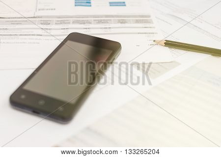 Bill and smart phone with pencil on table office