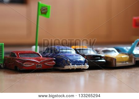 Cars toys are looking at race track.