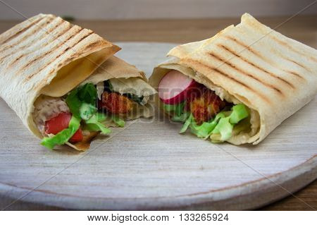 image of a doner kebab on white plate with vegetables