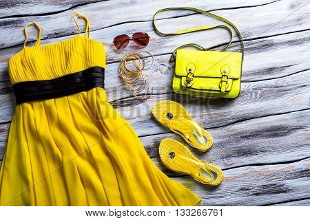 Yellow dress and lime handbag. Dress with sunglasses and bracelets. Woman's clothing on white table. Low prices for summer apparel.