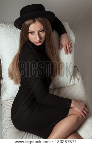 Beautiful stylish young woman with blonde long hair in black dress and hat sitting on a chair in studio