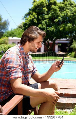 Young Man Sitting By Pool Holding Cellphone