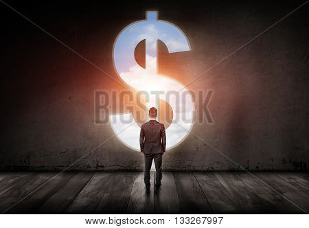 Well-dressed man standing in a big room in front of big silver dollar sign with blue sky inside it. Symbol of power, money and freedom. Targeting success and happiness. Back view.