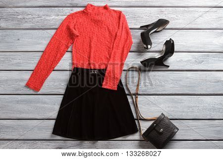 Red top and black skirt. Dark heel shoes and handbag. Spring sale in brand shop. Attractive female clothes and accessory.
