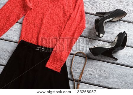 Black skirt and heel shoes. Red top with long sleeves. Luxury clothing on wooden table. Femininity and charm.