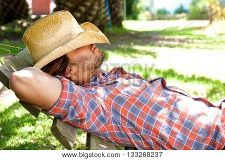 Young Man Lying On Hammock Resting With Hat