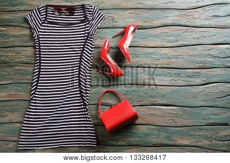 Striped dress and heel shoes. Red purse and sunglasses. Girl's casual evening outfit. Glossy shoes on high heel.