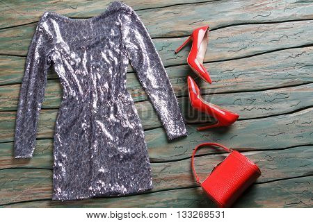 Glossy dress of silver color. Red heels and evening dress. Designer clothing for girls. Green wooden shelf with clothes.