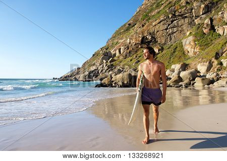 Attractive Male Surfer Walking On Beach With Surfboard