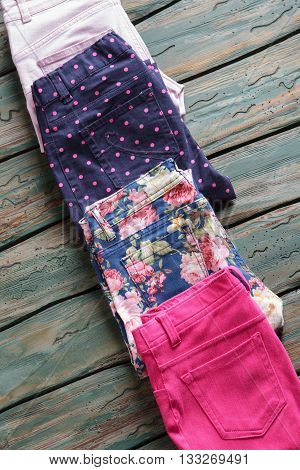 Pants with pink floral print. Folded trousers of navy color. New cotton pants on shelf. Quality items in outlet store.