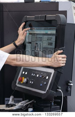 Automated workplace, engineer's hand on the working computer panel of industrial machinery