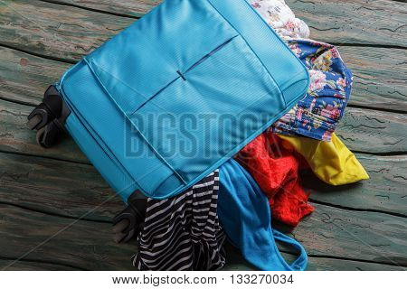 Blue overfilled suitcase. Luggage bag filled with clothing. Suitcase on green wooden floor. Vacation is waiting.
