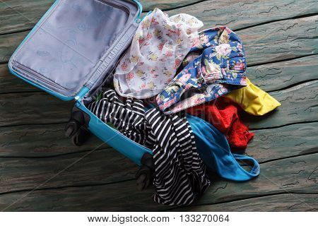Opened suitcase with clothes. Crumpled clothes inside luggage bag. You have forgotten something. Leaving home in a hurry.