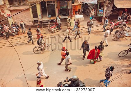 VARANASI, INDIA - JANUARY 4, 2016: Top view on people walking and cyclists riding on busy street of indian city on January 4, 2016. Varanasi urban agglomeration had a population of 1435113
