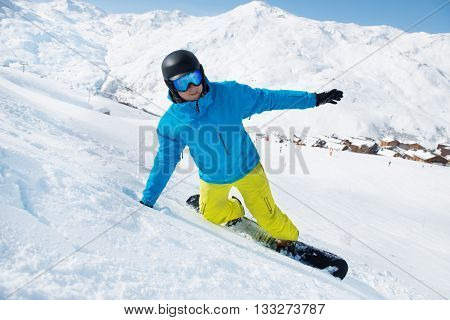 Happy snowboarder at the ski resort on a sunny day