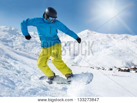 Active snowboarder jumping high in the mountains