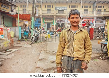 VARANASI, INDIA - JAN 4, 2016: Unidentified kid in dirty clothes standing on poor indian street with local stores and repair shops on January 4, 2016. Varanasi urban agglomeration had population of 1435113