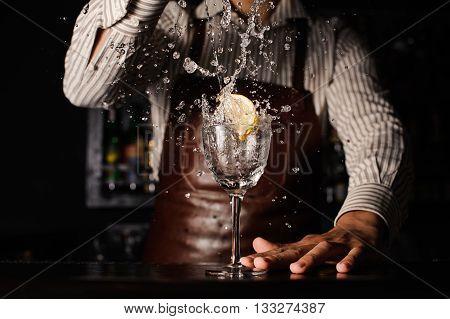 splash in a glass with lemon on bar barman on background