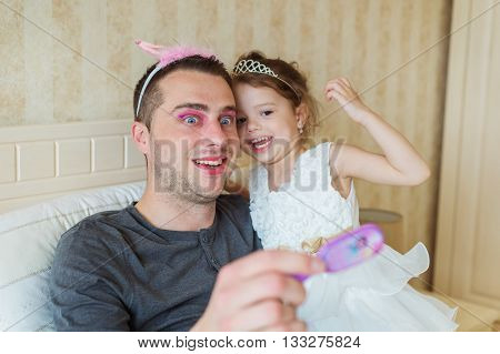Cute little girl in princess dress that put on colorful make up on her father
