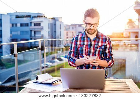 Young businessman working on a laptop computer, standing on the balcony, writing on smart phone