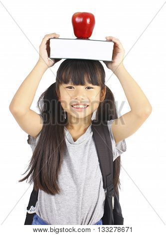 Cute girl holding book and apple on the head