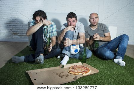 group of friends fanatic football fans watching soccer game on television with beers and pizza on grass carpet emulating stadium pitch looking nervous and anxious suffering stress