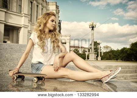 Fashion young girl model in jean shorts with long blond hair with skateboard. Urban youth style in town. Fashion concept