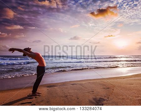 Vintage retro effect hipster style image of young sporty fit woman doing yoga Sun salutation Surya Namaskar pose Hasta Uttanasana on tropical beach on sunset
