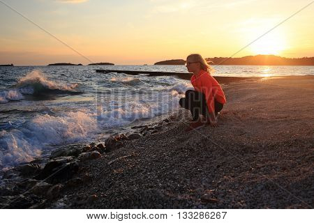 young girl is sitting on beach of ocean at sundown