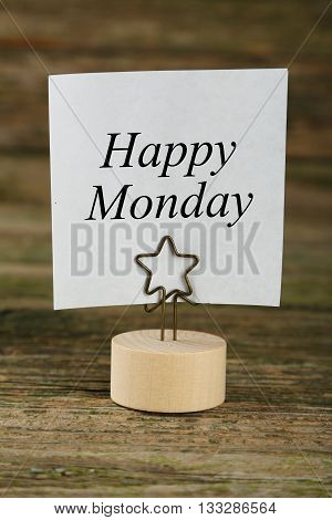 White note paper on a holder on brown wooden background, happy monday