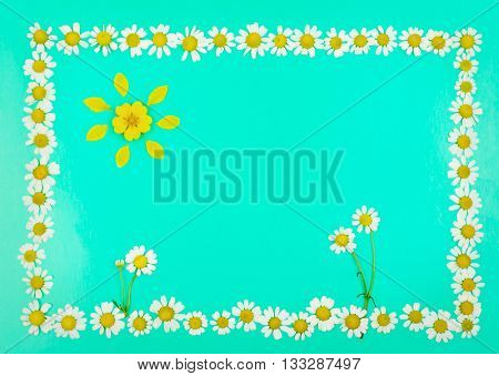 Frame with flowers and sun of daisies on light blue background. top view