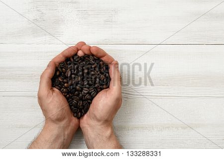 Close-up hands of man holding a handful of coffee beans with copy space. Top view composition. Grain selection. Workplace coffee maker. Coffee house. Uplifting mood. Coffee break.