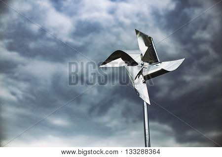 metal pinwheel on a background of the storm sky. silver pinwheel spinning in the wind against a dark sky. copy space for your text