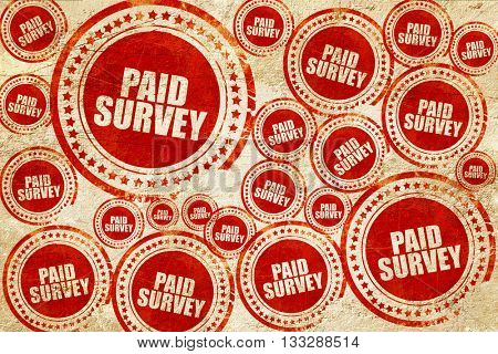 paid survey, red stamp on a grunge paper texture