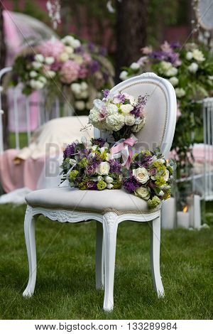 Beautiful wedding bouquet of colorful flowers on a vintage chair on the nature in sunset light decorations preparing for the wedding details boudoir