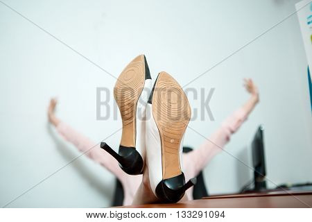 Relaxed business woman sitting in a chair with legs over the table.