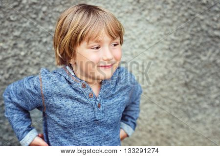 Fashion portrait of adorable little boy of 4-5 years old wearing blue sweatshirt, standing against grey wall