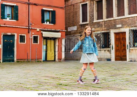 Outdoor portrait of adorable little girl of 7-8 years old, little kid travel in Italy. Child playing on the street of Venice.