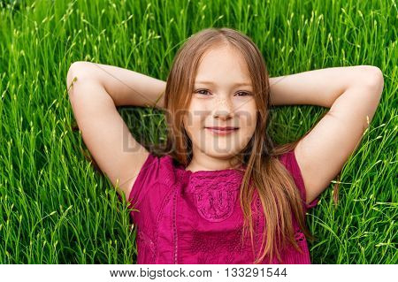 Young little girl resting outdoors. Close up outdoor portrait of adorable little girl of 8-9 years old laying on fresh lavender grass